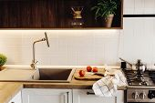 Wooden Board With Knife, Tomatoes On Modern Kitchen Countertop Near Granite Sink And Steel Faucet. C poster