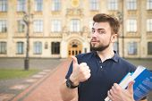 Portrait Of A Handsome Student Standing With Books In The Hands Of The University Building Backgroun poster