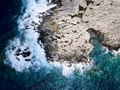 Aerial above stormy sea waves crashing against rock coastline outcrops poster