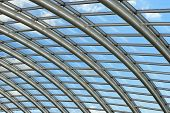 image of purlin  - Silver metal curved roof joists in a conservatory with glass window panes in between and a blue sky and clouds beyond - JPG