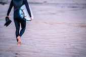 Surfing Instructor Carrying His Shoes And Surfing Board On The Beach In Saint Ives, Cornwall, Uk poster