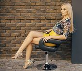 Office Worker. Woman With Long Blond Hair And Makeup, Beauty. Sexy Woman In Fashionable Clothes Sit  poster