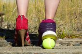 Ladies Legs, One Foot In The Court Shoe And The Other Foot In A Sports Shoe And A Tennis Ball.a Woma poster