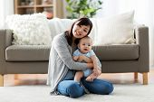 family and motherhood concept - happy smiling young asian mother with little baby at home poster