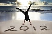 stock photo of new years  - happy new year 2012 on the beach with sunrise - JPG