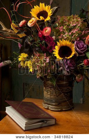 Rustic still life with autumn flowers and leather bound book