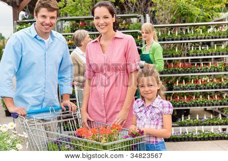 Young family shopping at garden centre flower market