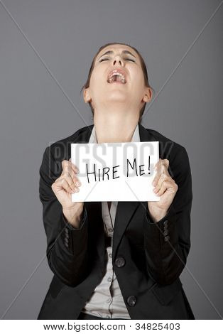 """Business woman holding a card board with the text message """"Hire me"""" and beging for a job."""