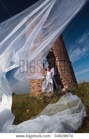 Wedding shot of sexy passion between bride and groom staying against abandoned ruins