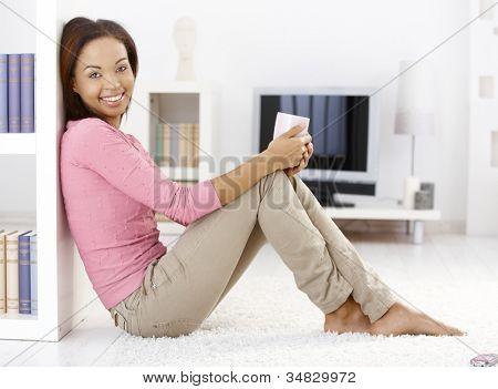 Retrato de mulher bonita sentada no chão da sala de estar com caneca de chá na mão em casa, olhando a camer