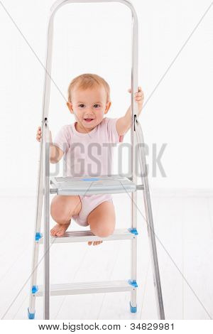 Cute baby girl climbing on ladder, smiling.
