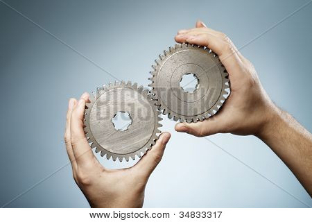 Man holding a pair of old metallic cog gear wheels in his hands.