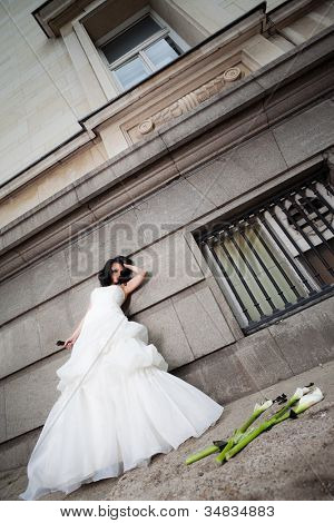 Unhappy bride with wedding dress leaning on a wall, holding broken bottle in one hand