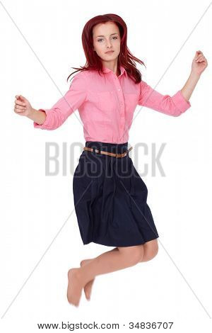 Young attractive redhead female in pink shirt and blue skirt jump up, isolated