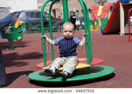 Child Sitting On Roundabout