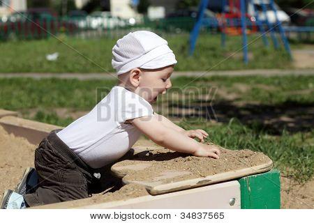 Happy Boy Playing In Sandbox