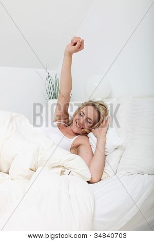 Woman Stretching Against Her Pillows