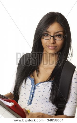 Attractive young female student holding school supplies and laptop computer