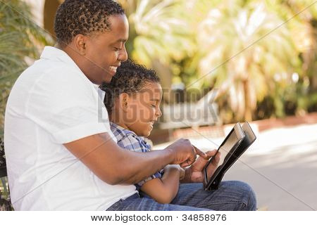 Happy African American Father and Mixed Race Son Having Fun Using Touch Pad Computer Tablet Outside.