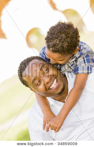 Happy African American Father and Mixed Race Son Playing Piggyback in the Park.