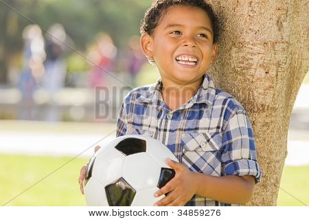 Mixed Race Boy Holding Soccer Ball in the Park Against a Tree.