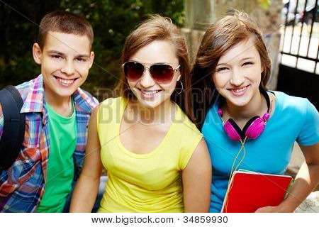 Close-up portrait of three school friends smiling at camera