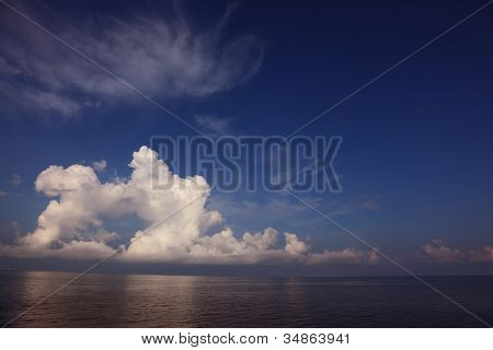 The sea in tropics. Clouds of the freakish form are reflected in a smooth water surface