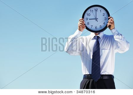 Portrait of a businessman holding a clock against blue background
