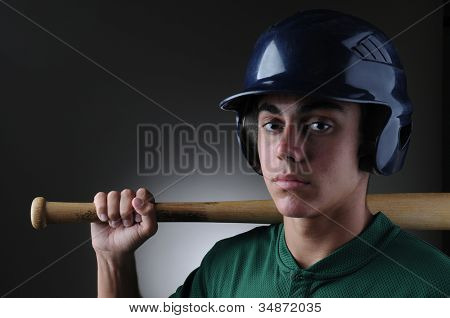 Closeup of a Teenage baseball player holding a bat on his shoulder. Horizontal format with a light to dark gray background.