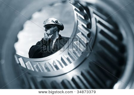 engineer seen through the shaft of a giant gear wheel, duplex blue toning concept