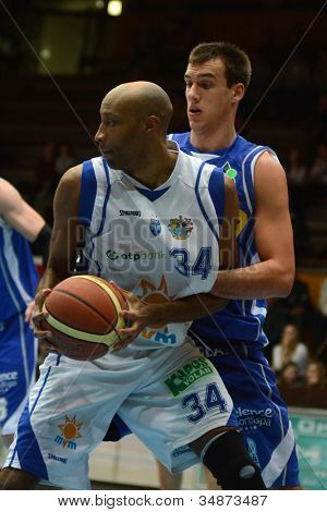 KAPOSVAR, HUNGARY - FEBRUARY 22: Charles Gosa (in white) in action at a Hungarian Cup basketball game with Kaposvar (white) vs. Fehervar (blue) on February 22, 2012 in Kaposvar, Hungary.