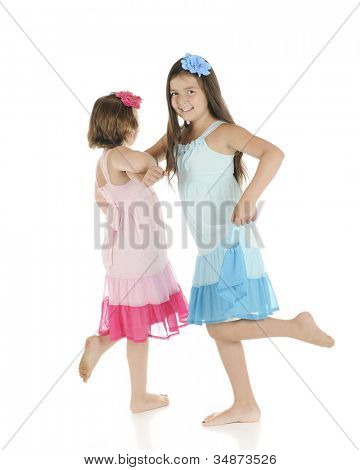 Two barefoot elementary girls frolicking with each other.  They're wearing identical outfits except one is pink, the other blue.
