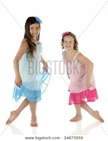 Two elementary girls happily dancing with each other.  They're wearing identical outfits except one is blue, the other pink.  On a white background.
