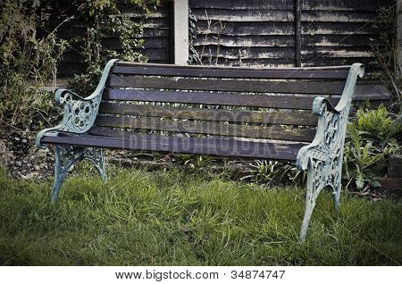 Vintage bench in a garden, retro style picture with film grain and vignette