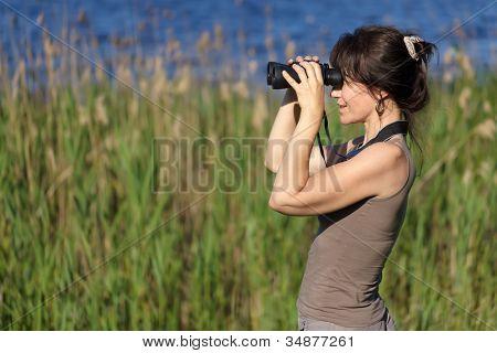 mulher, observando a vida selvagem com binóculos em área de pântano