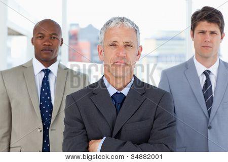 Gerente sério em pé na frente de seus dois jovens executivos