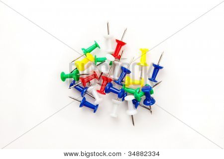 Large group of muti coloured pushpins against a white background