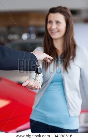Brunette receiving car keys in his hand in a garage