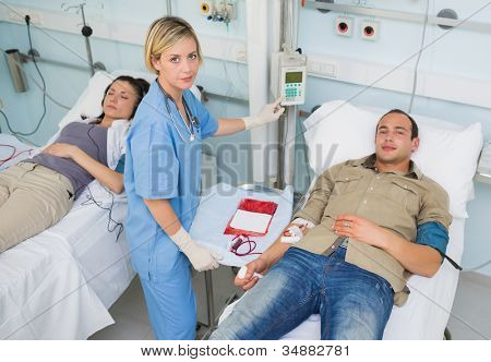 Nurse touching monitor next to transfused patients in hospital ward