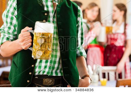 Young people in traditional Bavarian Tracht in restaurant or pub, one man is standing with beer stein in front, the group in the background