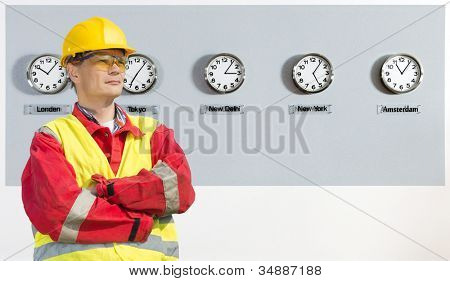 worker, wearing coveralls, safety goggles and a hard hat in front of a wall, with five clocks, displaying the time in various parts of the world