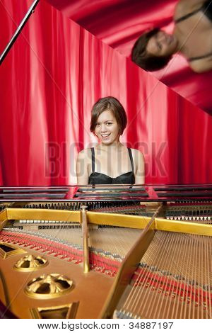 Formal concert on stage as a pretty young woman plays classical music on a grand piano