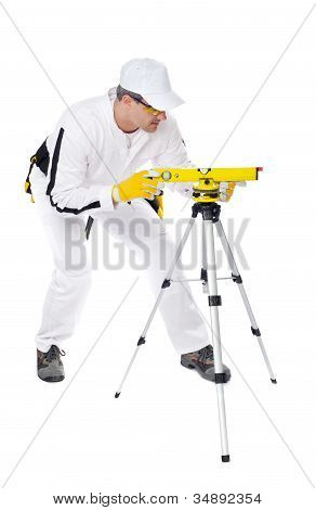 Construction Worker In White Coveralls Looking Instrument Level