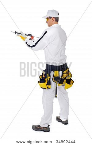 Construction Worker In White Overalls Holding A Gun Silicone Sealant Glue Tools On White Background