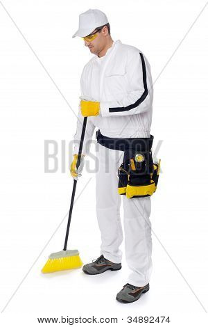 Construction Worker In White Overalls Sweeping With A Broom On White Background