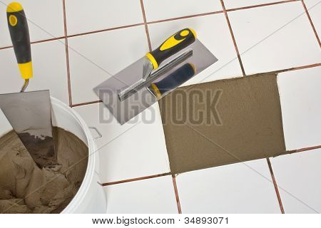 Repaired Old White Tiles Floor With Trowel And Tile Adhesive
