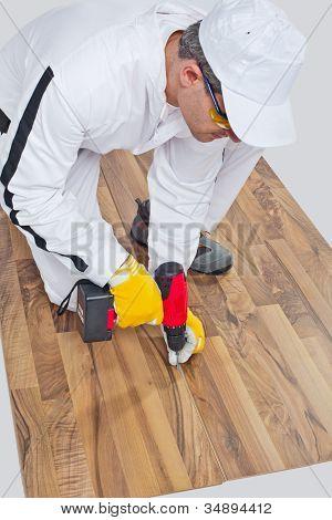 Worker Drills A Screw Wooden Floor Cracks