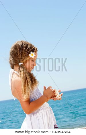 Cute Girl Holding Shells On Sunny Beach.