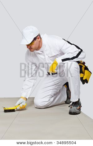 Worker With Wire Brush Cleans The Cement Substrate