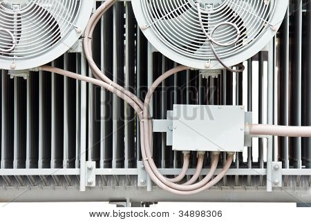 An Industrial Ventilation Fan Attached To A Building With Cage Guard